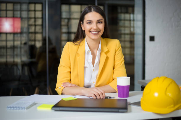 Portrait of beautiful architect sitting at the desk and looking at camera stock photo