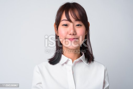 Studio shot of beautiful Japanese businesswoman against white background
