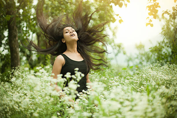 Portrait of Beautiful Asian girl in meadow doing hair toss. stock photo