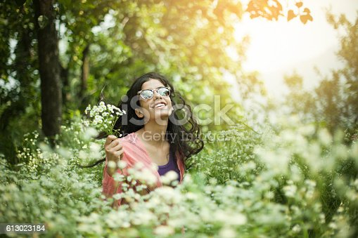 Outdoor day time image shot in natural light of a Beautiful Asian girl in the middle of nature surrounded by beautiful little white flower plants. She is wearing sunglasses and holding bunch of white wild flowers in lush meadow against glowing sun light. Waist up, one person, horizontal composition with copy space and selective focus.