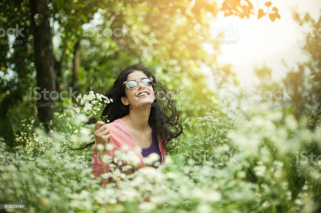 Portrait of Beautiful Asian girl in meadow holding wild flowers. stock photo