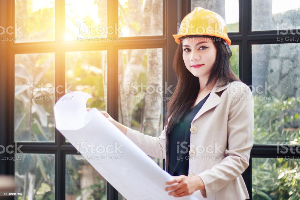 portrait of beautiful Asian woman architect builder with yellow helmet hard hat studying blueprint plan of the rooms, serious civil engineer working with documents on construction site stock photo