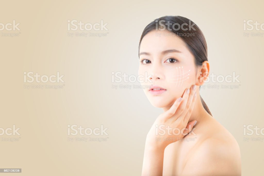 Portrait of beautiful asian woman makeup of cosmetic, girl hand touch cheek and smile with arrow antiaging, face of woman beauty perfect wellness on yellow background with skin healthcare concept. stock photo
