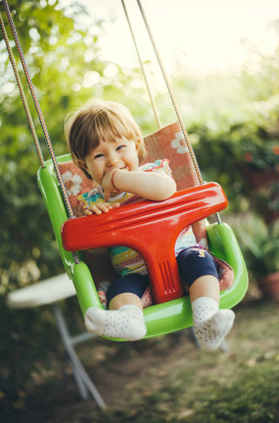 Portrait of Beautiful Baby girl enjoying in the swing during summer stock photo