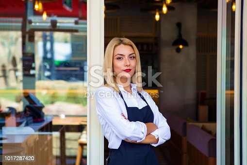 1066358064istockphoto Portrait of beautiful barista in apron with tablet in cafe. 1017287420
