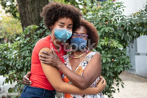Portrait of beautiful black mother and daughter embracing each other facing camera both wearing protective facemasks - Pandemic lifestyles