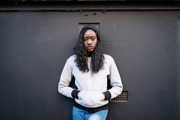 retrato de mulher negra linda de jeans e jumper contra parede preta - girl power provérbio em inglês - fotografias e filmes do acervo