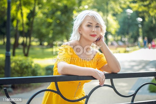 977601820 istock photo Portrait of beautiful blond 40-year-old woman outdoor 1166382326