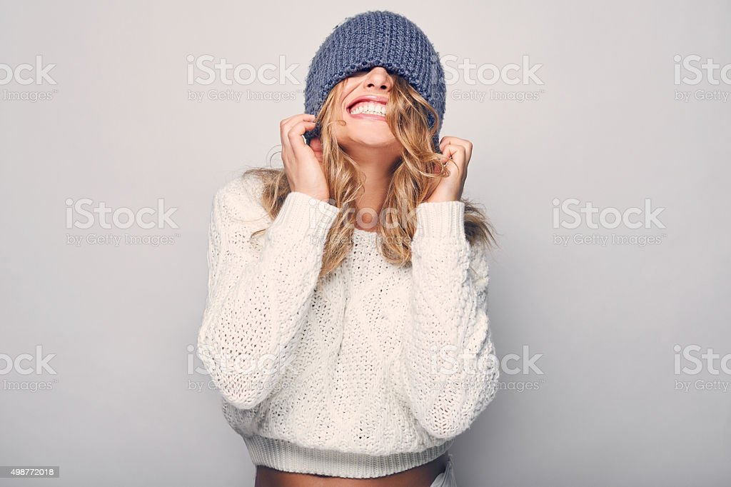 Portrait of beautiful blond woman in white in white sweater and blue...