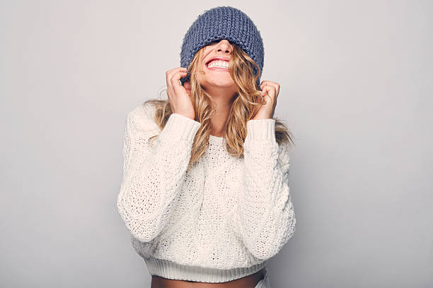 Portrait of beautiful blond woman Portrait of beautiful blond woman in white in white sweater and blue hat warm clothing stock pictures, royalty-free photos & images