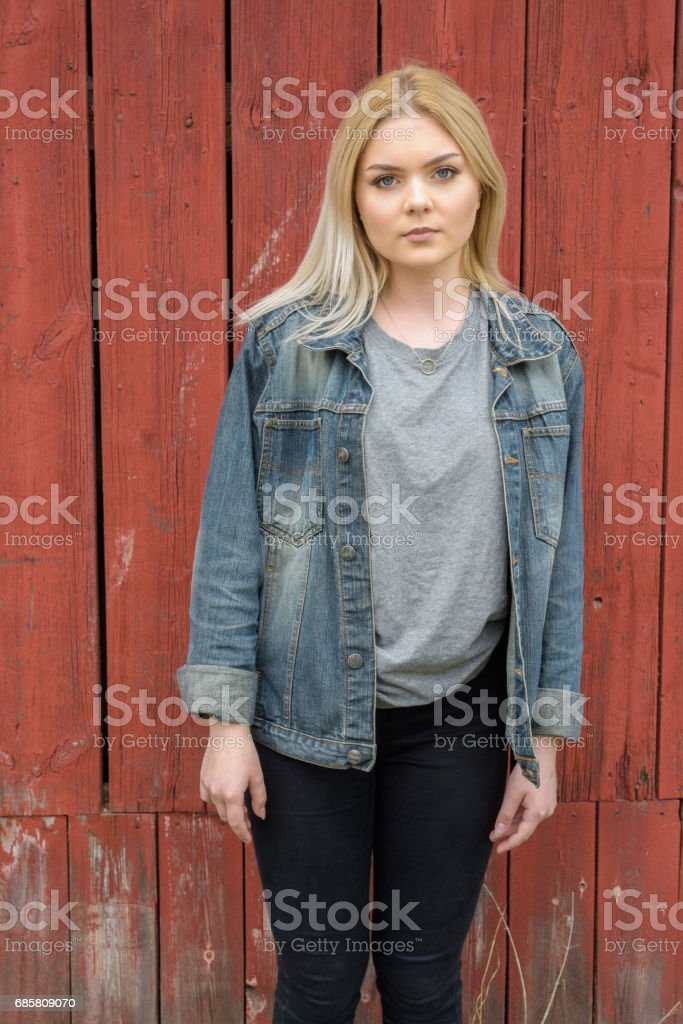 Portrait of beautiful blonde Scandinavian teenage girl against red traditional wooden building wall - foto stock