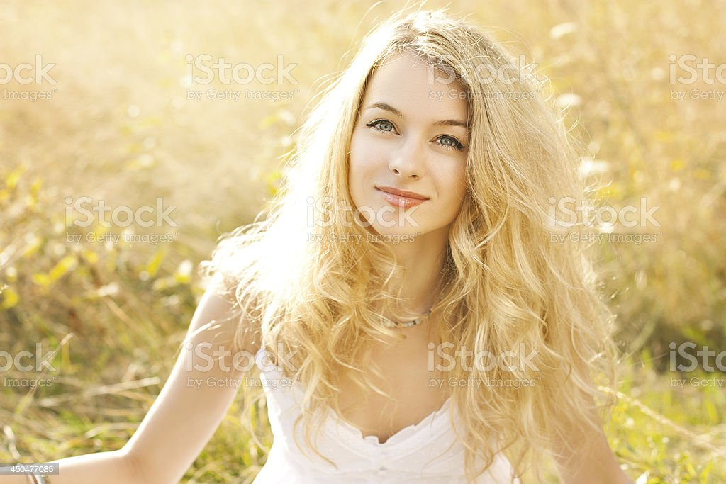 Portrait of beautiful blonde woman sitting on a field stock photo