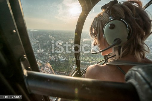 Portrait of beautiful blonde women enjoying helicopter flight. She is amazed by cityscape and wearing pilot headphones.