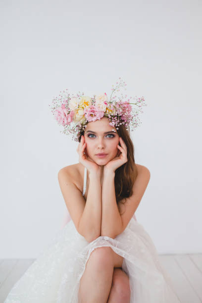 Portrait of beautiful bride with flower wreath on her head at white background stock photo