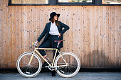 Portrait of beautiful brunette holding bicycle. Wooden background.