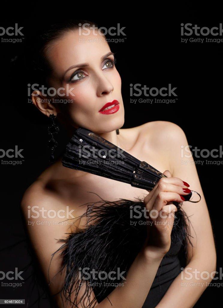 portrait of beautiful brunette woman with black fan in hands