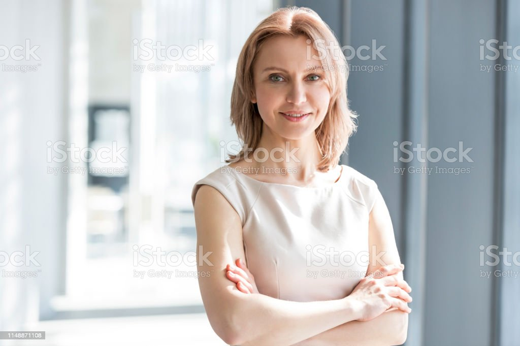 Portrait of beautiful businesswoman standing with arms crossed at office Portrait of beautiful businesswoman standing with arms crossed at office Adult Stock Photo
