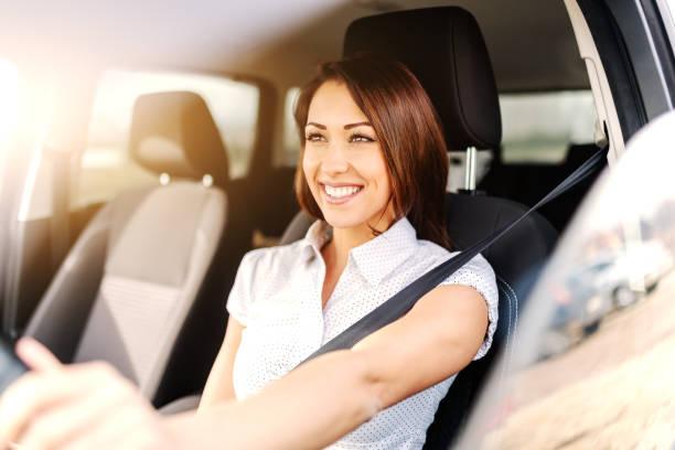 retrato da mulher caucasiano bonita com sorriso toothy e cabelo marrom que conduz o carro. mão no volante. - carro mulher - fotografias e filmes do acervo