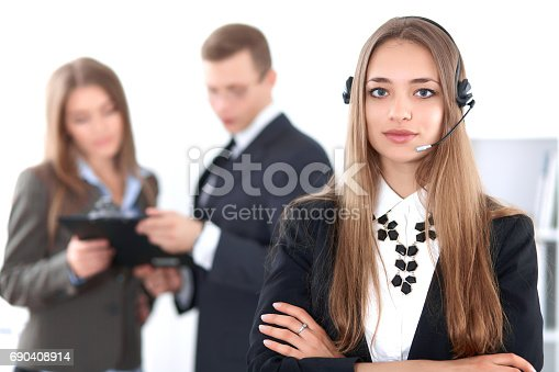 istock Portrait of beautiful cheerful smiling call operator on the background of business people. Successful call center concept 690408914