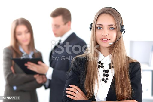 istock Portrait of beautiful cheerful smiling call operator on the background of business people. Successful call center concept 697622154