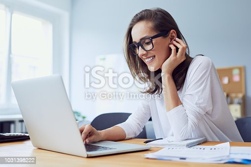 istock Portrait of beautiful cheerful young businesswoman working on laptop and laughing in home office 1031398222