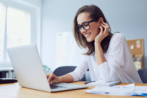 portrait of beautiful cheerful young businesswoman working on laptop and laughing in home office - computer imagens e fotografias de stock