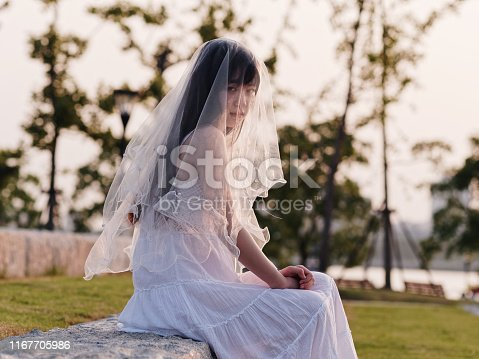istock Portrait of beautiful Chinese girl in white bride dress sitting and looking at camera with veil on head in windy dusk with blur meadow background, Beauty, lifestyle and summer Concept. 1167705986