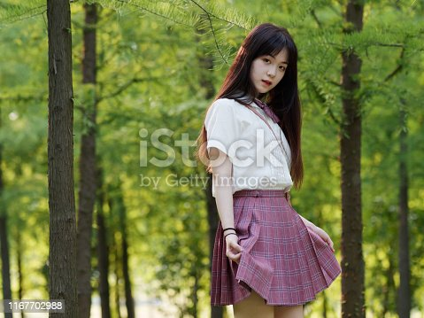 istock Portrait of beautiful Chinese girl in white shirt and pink skirt looking at camera with hands lifting dress in sunny summer forest, Beauty, lifestyle and summer Concept. 1167702988
