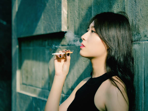 Portrait of beautiful Chinese girl smoking outdoor and thinking about problems, seems a little bit lost, in vintage mode. stock photo
