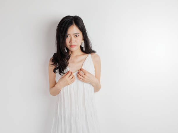 Portrait of beautiful Chinese woman in white dress posing with white wall background, young girl puts her hands on her chest and smiling at camera. stock photo