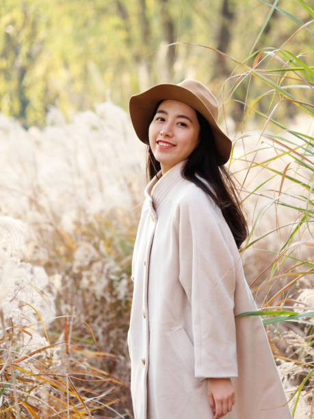 Portrait of beautiful Chinese young woman in beige coat and hat posing and smiling at camera, charming Chinese girl with black long hair enjoy her leisure time outdoor. stock photo