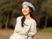 ウールのセーターと青いベレーの美しい中国の若い女性の肖像画は、ポケットに手で微笑み、黒い長い髪を持つ魅力的な中国の女の子は、屋外で彼女の余暇を楽しみます。