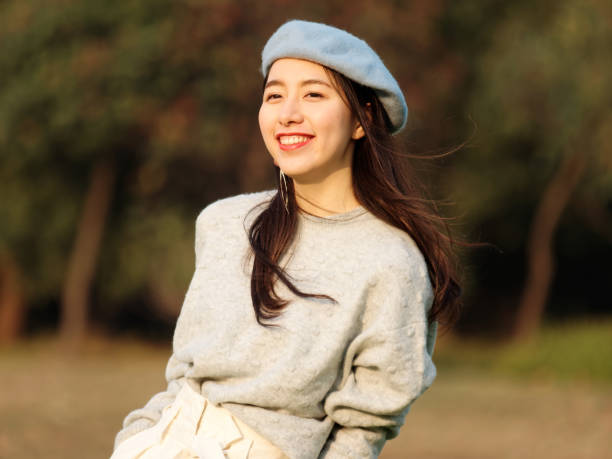 Portrait of beautiful Chinese young woman in woolen sweater and blue beret smiling with hands in pocket, charming Chinese girl with black long hair enjoy her leisure time outdoor. stock photo