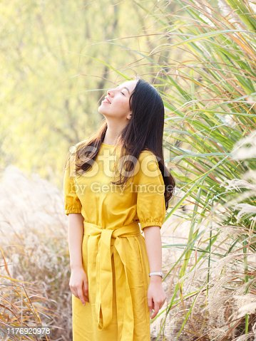 istock Portrait of beautiful Chinese young woman in yellow dress posing with eyes closed and smiling, charming Chinese girl with black long hair enjoy her leisure time outdoor. 1176920978