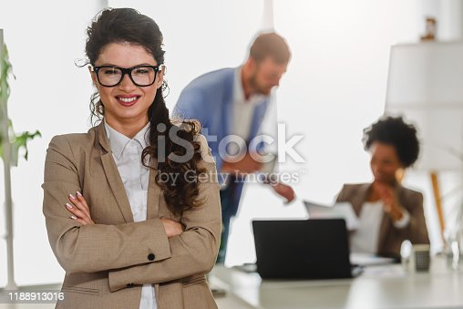 Portrait of beautiful confident young businesswoman at office in front of her colleagues