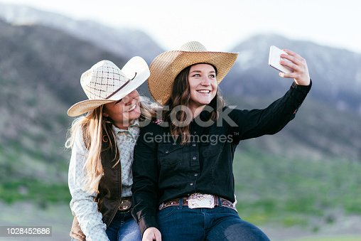 516318379 istock photo Portrait of beautiful cowgirls taking selfie with smartphone in USA 1028452686