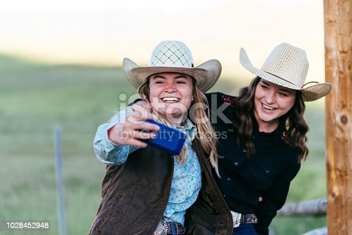 516318379 istock photo Portrait of beautiful cowgirls taking selfie with smartphone in USA 1028452948