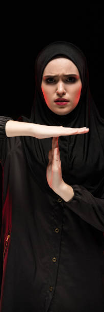 Portrait of beautiful desperate scared frightened young muslim woman wearing black hijab showing stop sign on black background stock photo