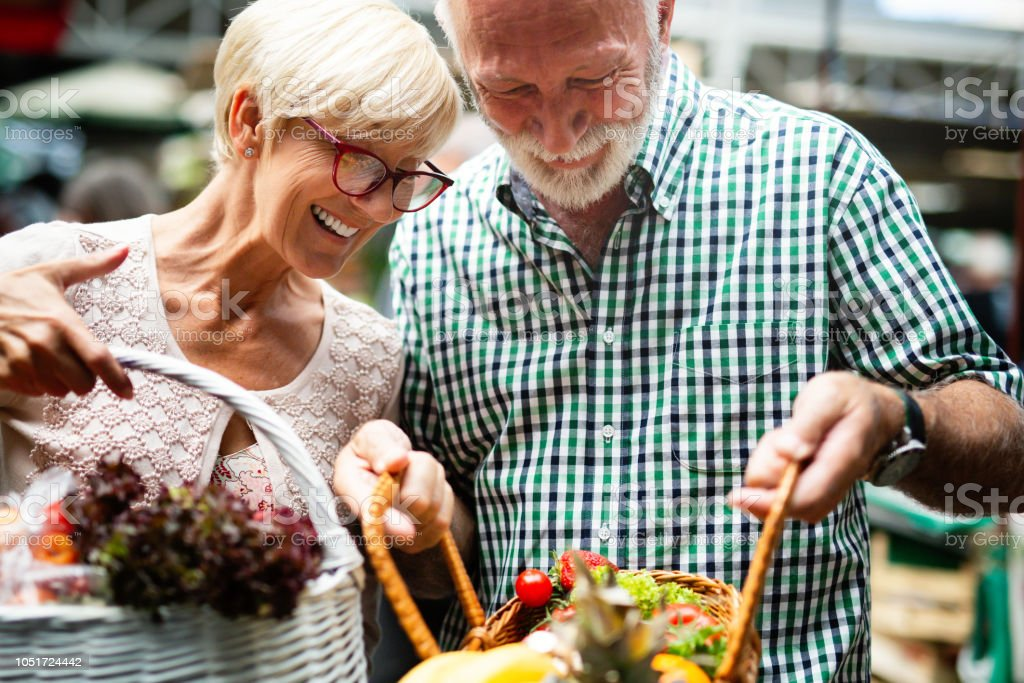 Portrait of beautiful elderly couple in market buing food stock photo