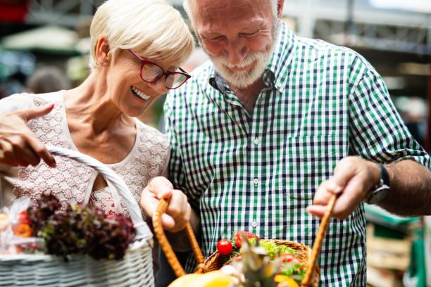retrato de lindo casal de idosos em comida de gravação do mercado - dia do cliente - fotografias e filmes do acervo
