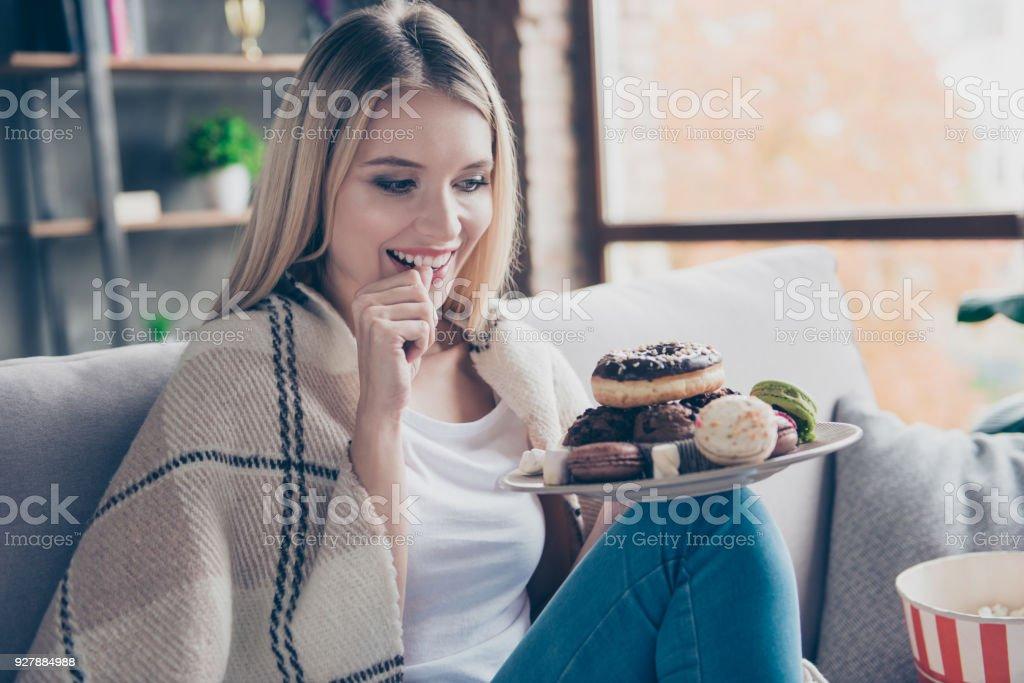 Porträt von schöne emotionale charmante attraktive süße Äpfel Frau sitzt auf dem Sofa im Wohnzimmer, Halteplatte von Donuts und Makronen, zufrieden auf der spannenden Suche – Foto