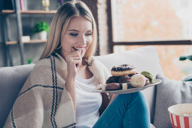 Portrait of beautiful emotional charming attractive sweet toothy woman sitting on sofa in living room, holding plate of donuts and macaroons, looking exciting satisfied stock photo