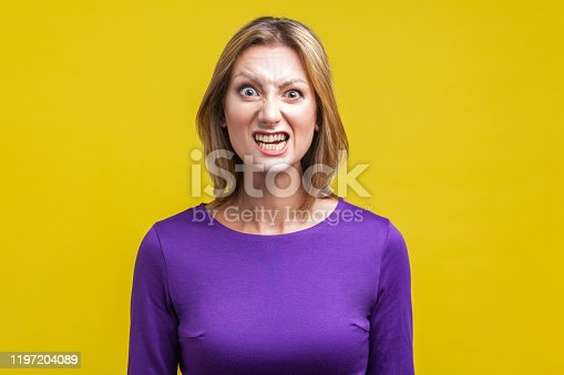 808681534 istock photo Portrait of beautiful emotional woman with clenched teeth pretending to be aggressive. indoor studio shot isolated on yellow background 1197204089