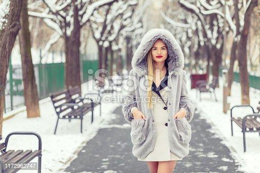 Portrait of beautiful fashion girl walking outdoors in park enjoying show