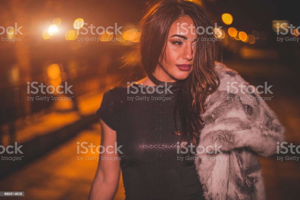 Portrait of beautiful fashionable woman walking on the river jetty at night stock photo