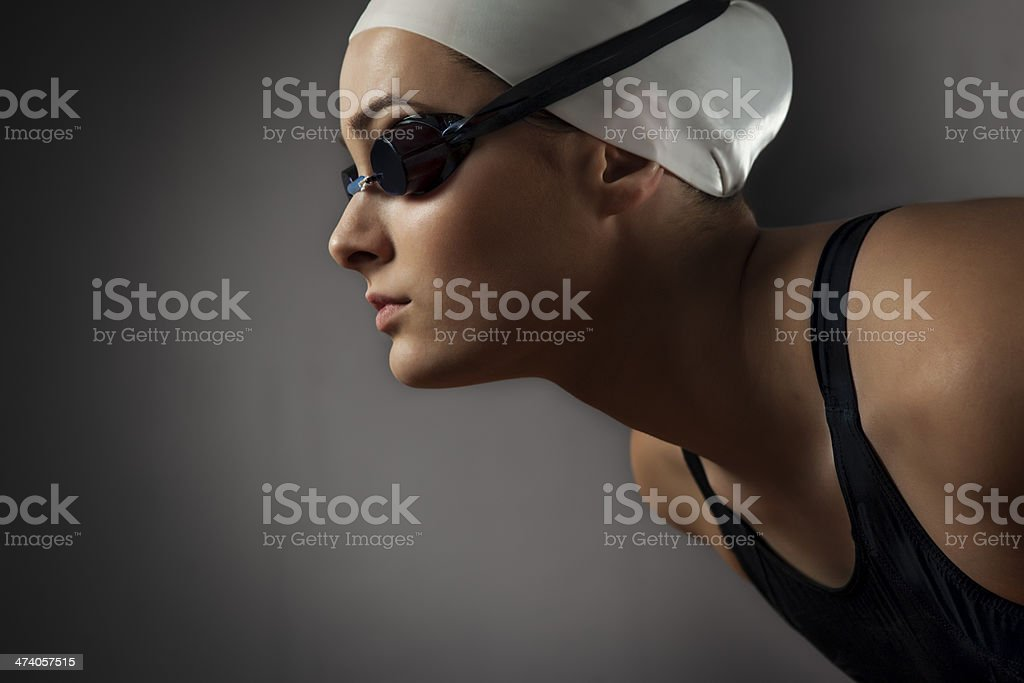 Portrait of beautiful female swimmer getting ready for jump stock photo