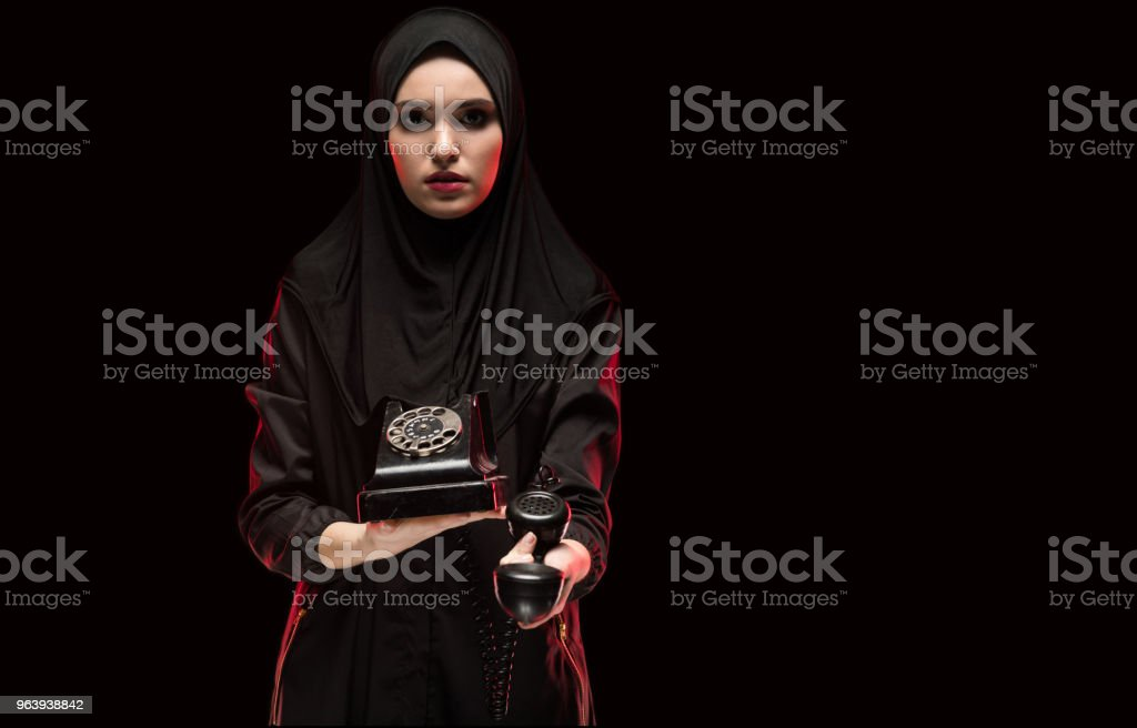 Portrait of beautiful frightened scared young muslim woman wearing black hijab offering telephone to call as choice concept on black background - Royalty-free Adult Stock Photo