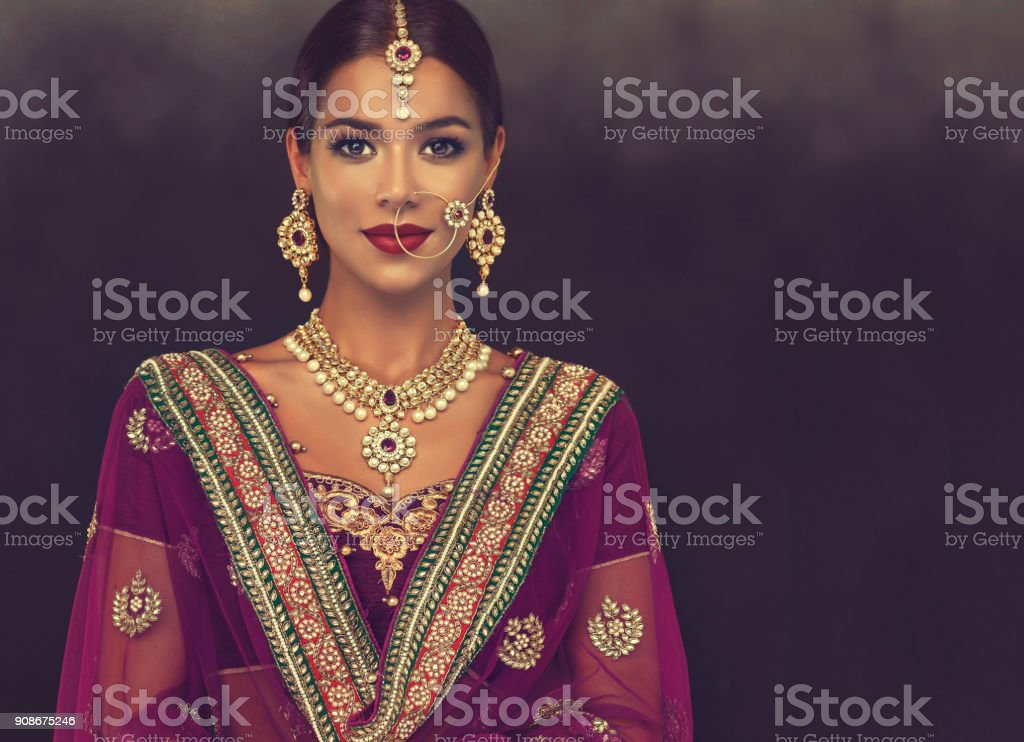 Portrait of beautiful girl dressed in a traditional indian national suit, jewelry set, blouse and shawl (dupatta). stock photo