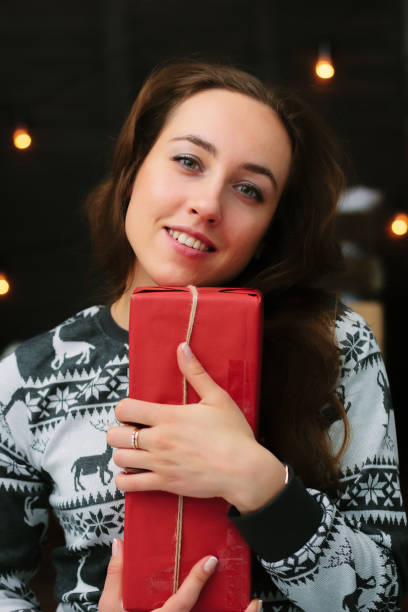 Portrait of beautiful girl holding red gift box near during christmas and smiling. stock photo