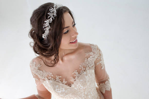 Portrait of beautiful girl in a luxurious wedding dress. Bride with beautiful decoration in her hair, smiling Portrait of a beautiful girl in a wedding dress. Bride in a luxurious dress on a white background diademe stock pictures, royalty-free photos & images